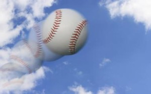 A photocomposition of a baseball in motion flying in the air over a partly cloudy sky.